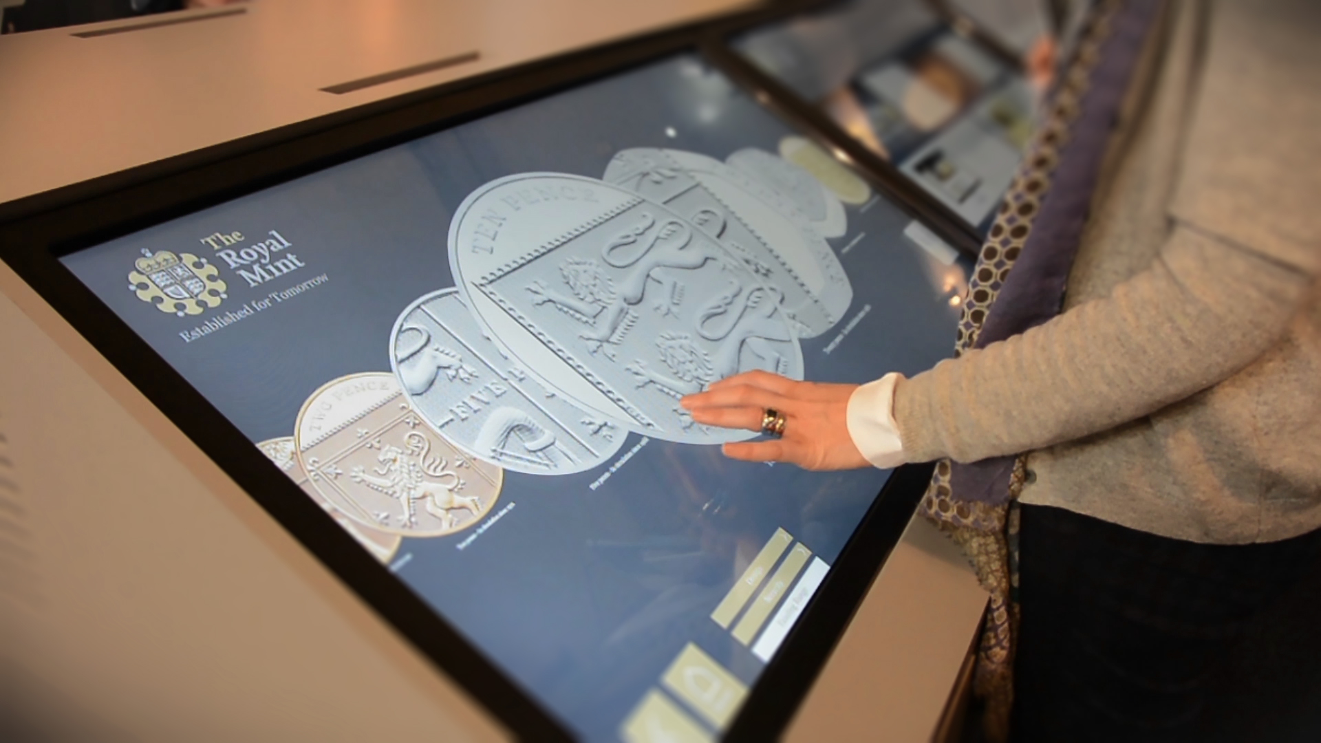 woman interacting with The Royal Mint interactive touchscreen software displayed on large monitor on white surface
