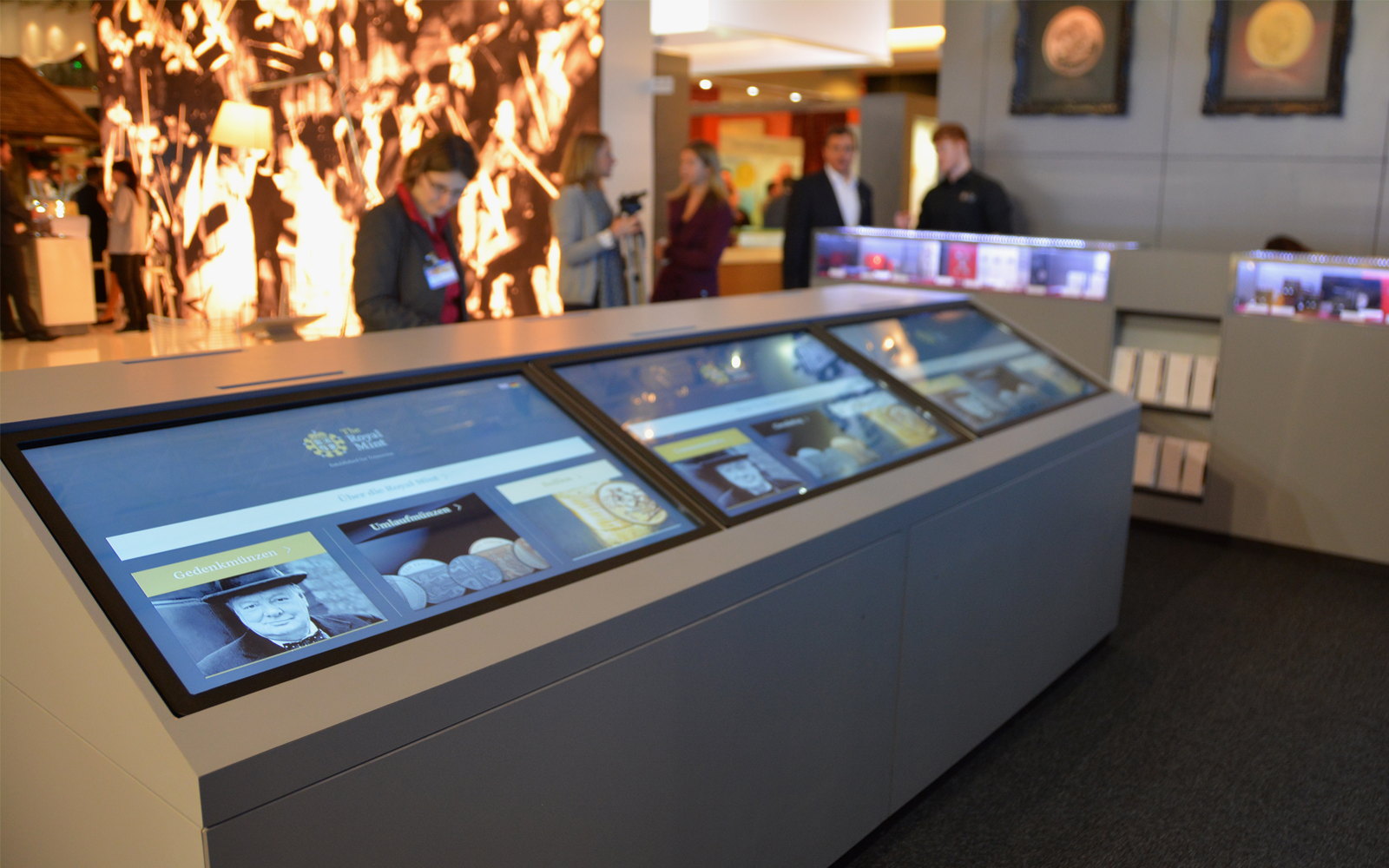 The Royal Mint interactive display software displayed on 3 large monitors