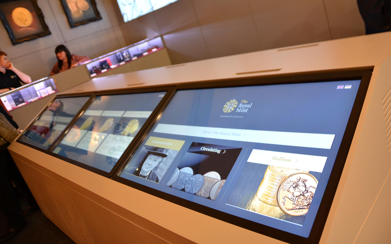 man and women interacting with The Royal Mint interactive touchscreen display software shown on large monitors