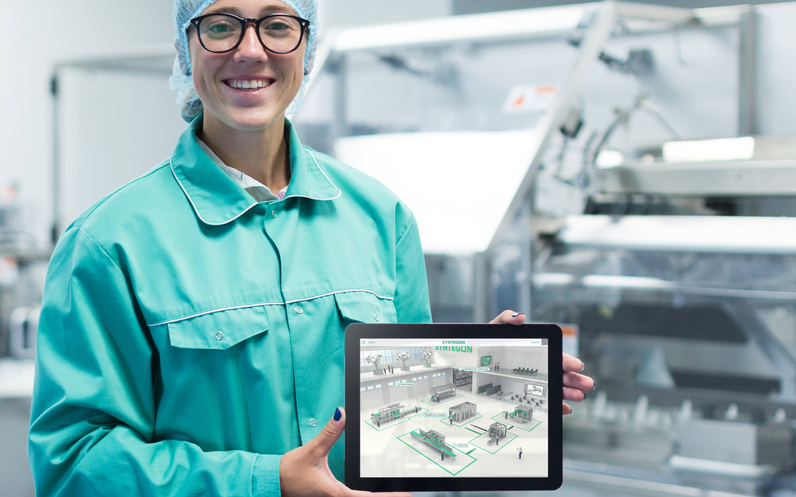 Syntegon employee smiling in manufacturing lab holding iPad showing touchscreen interactive presentation