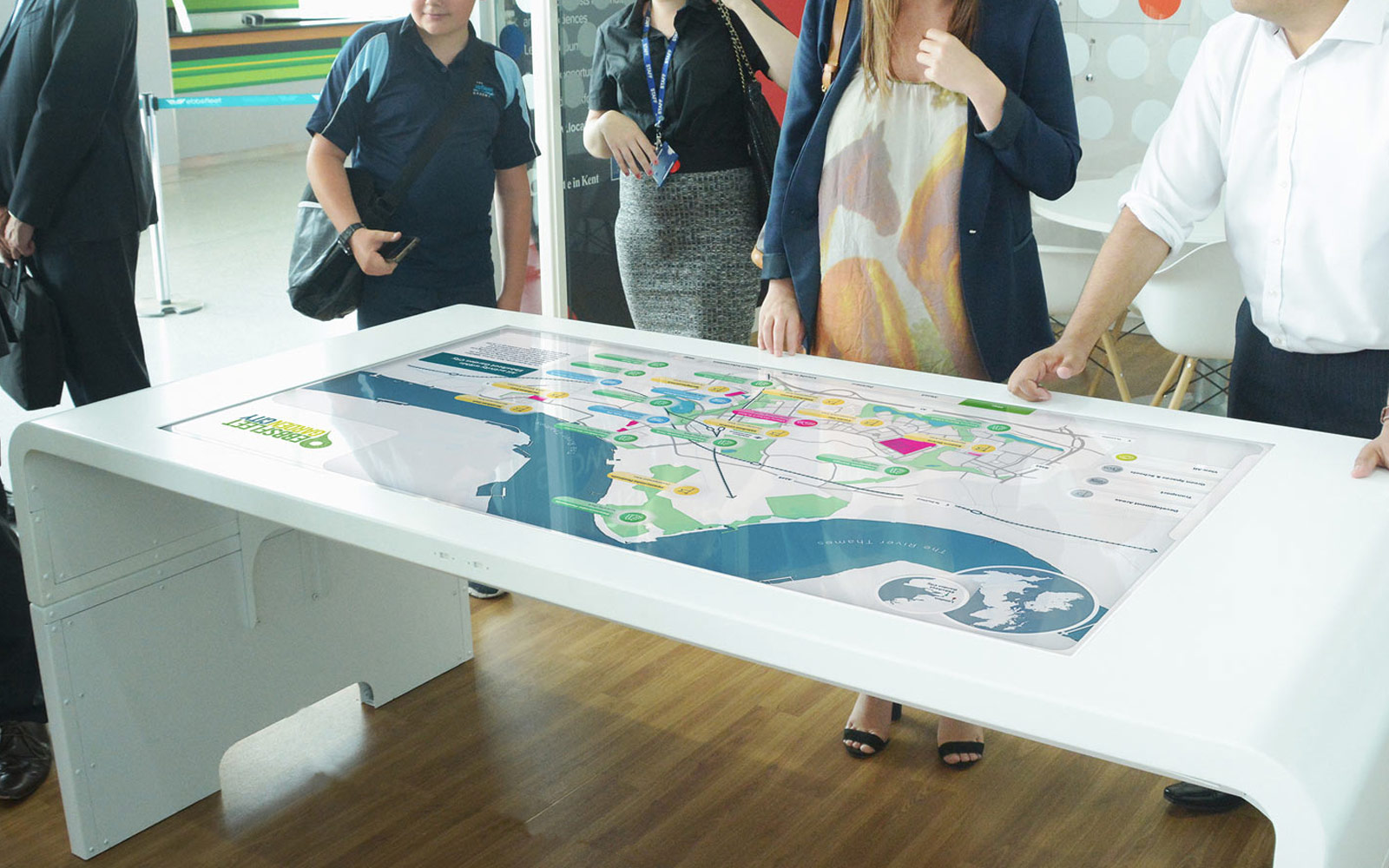 group of people interacting with Ebbsfleet touchscreen display on white table in office