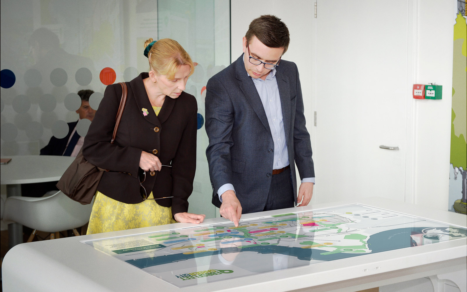 woman and man interacting with Ebbsfleet interactive touchscreen display on white table