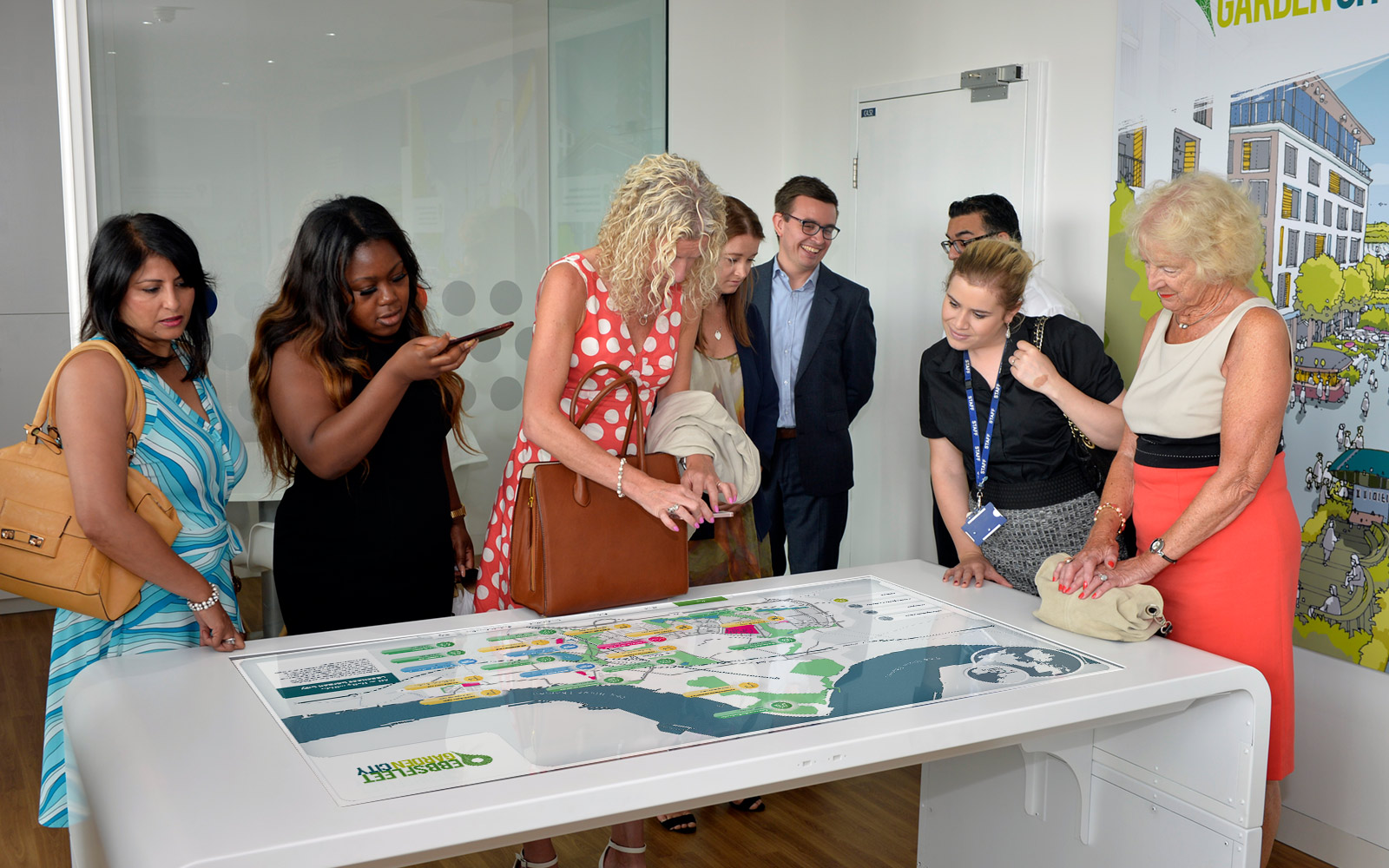 group of people smiling and interacting with ebbsfleet touchscreen display on white table in office