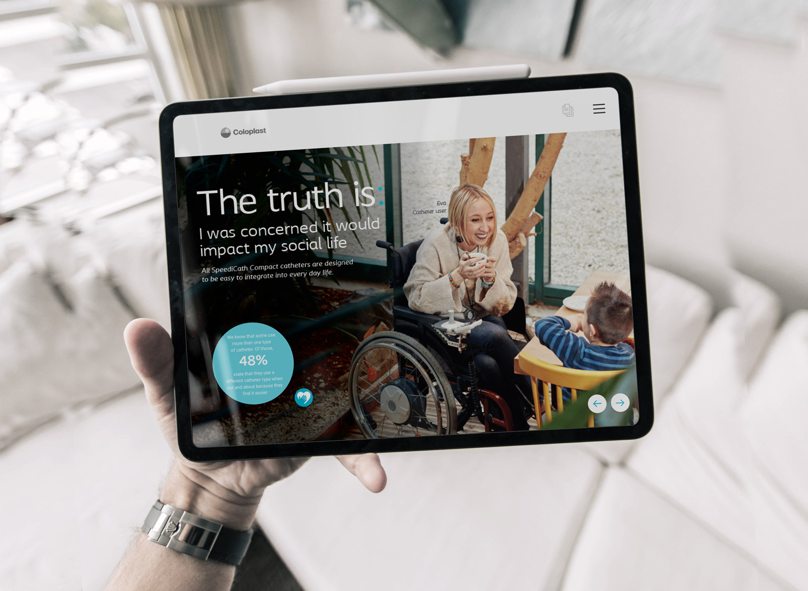 person holding black tablet displaying Coloplast interactive touchscreen digital presentation