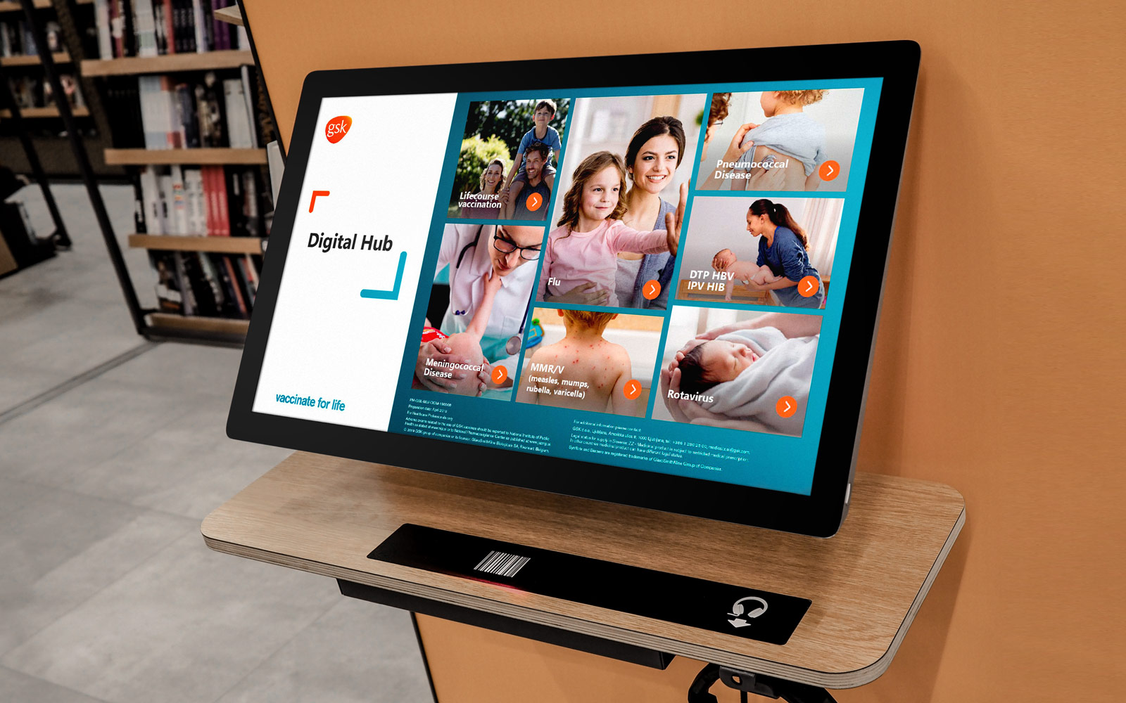 GSK interactive touchscreen display software digital hub page shown on large monitor in library