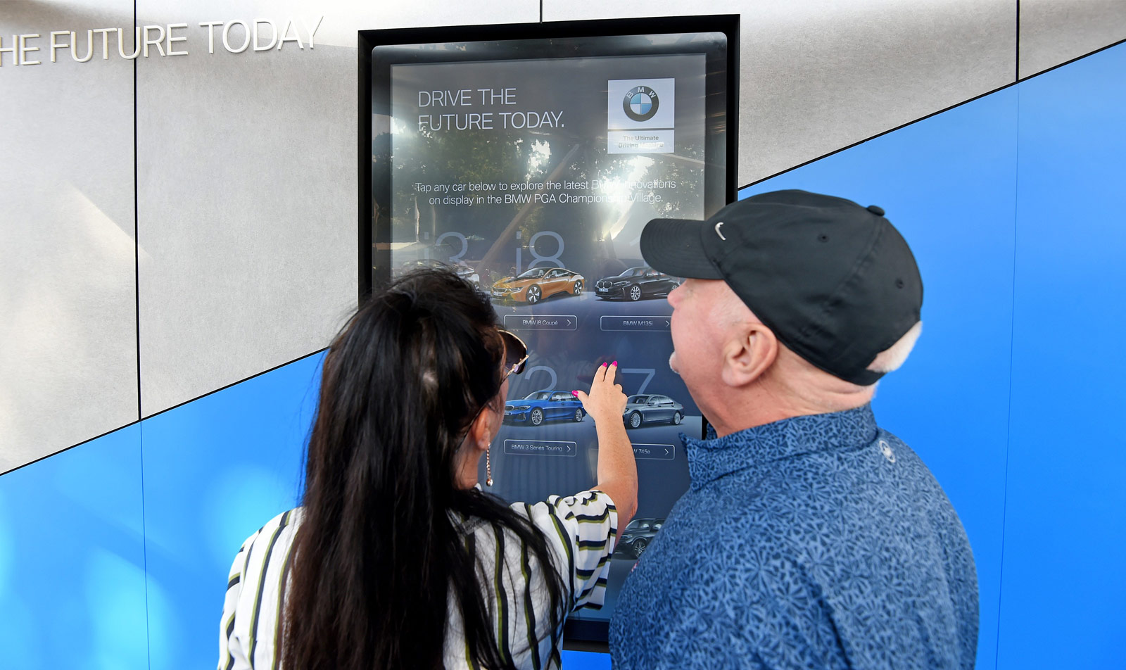 woman and man interacting with BMW interactive touchscreen app displayed on grey and blue wall