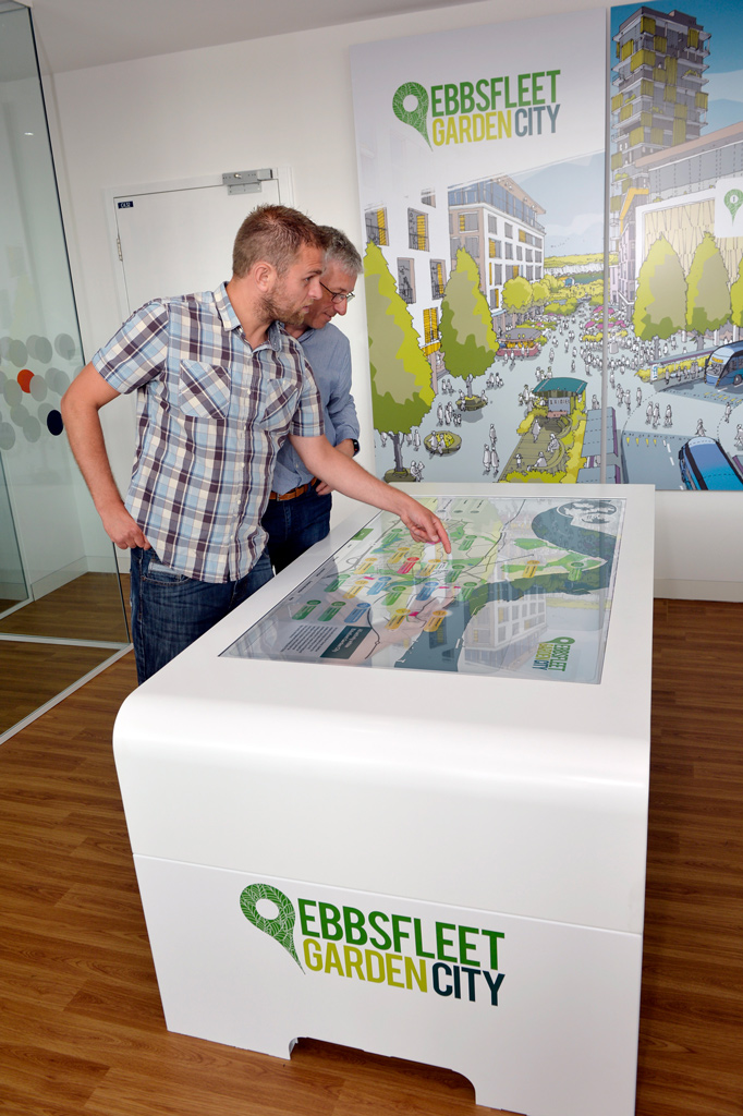 two men interacting with Ebbsfleet Garden City touchscreen presentation interactive map on large white monitor