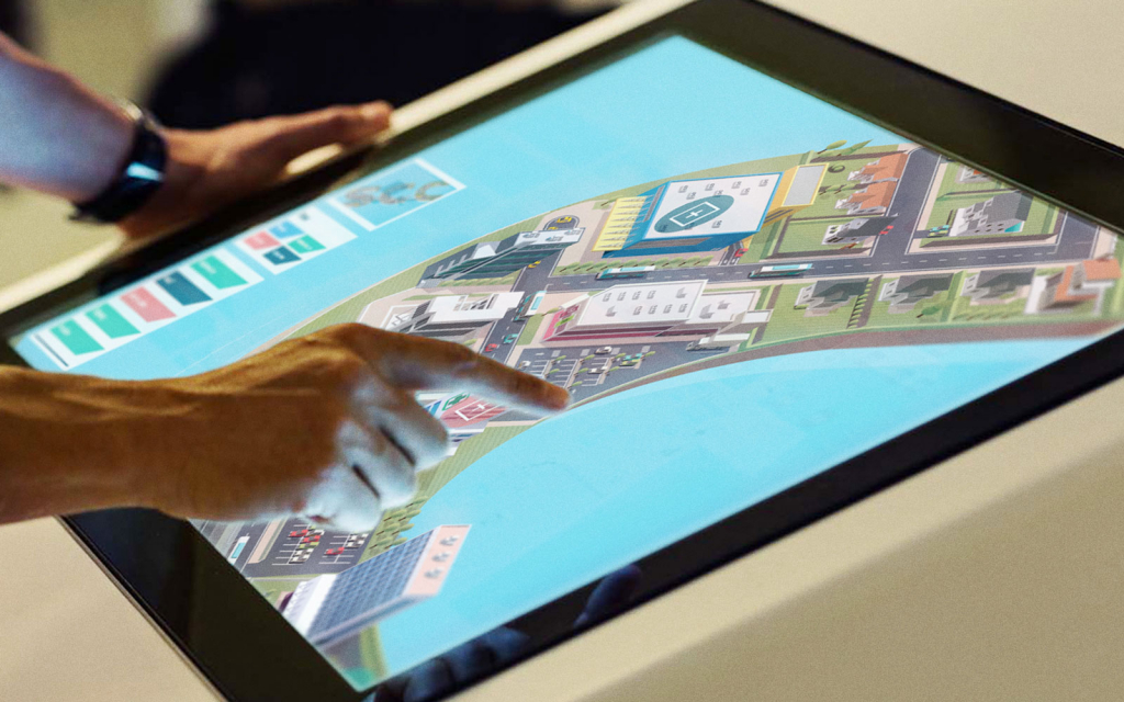 A user of a touchscreen experience exploring the cityscape designed for SCC.