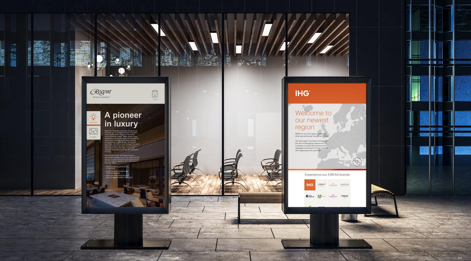 two large monitors displaying digital presentations outside office building IHG Regent