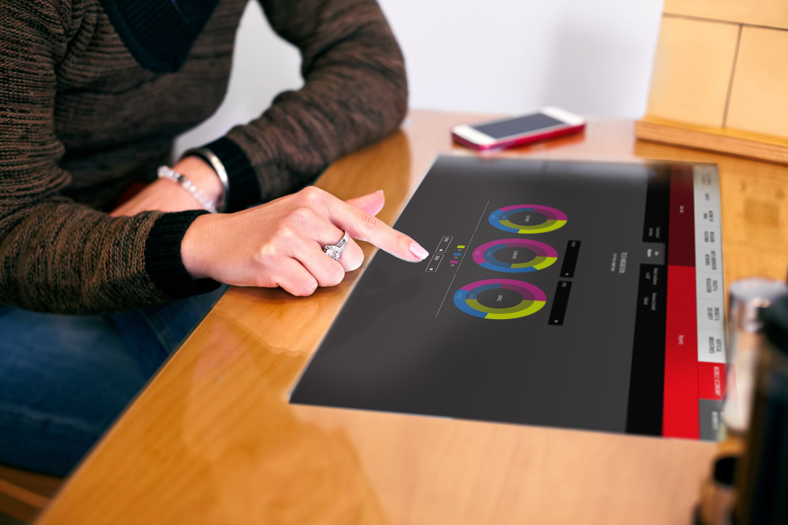 person wearing diamond ring interacting with interactive touchscreen presentation displayed on large monitor on wooden table