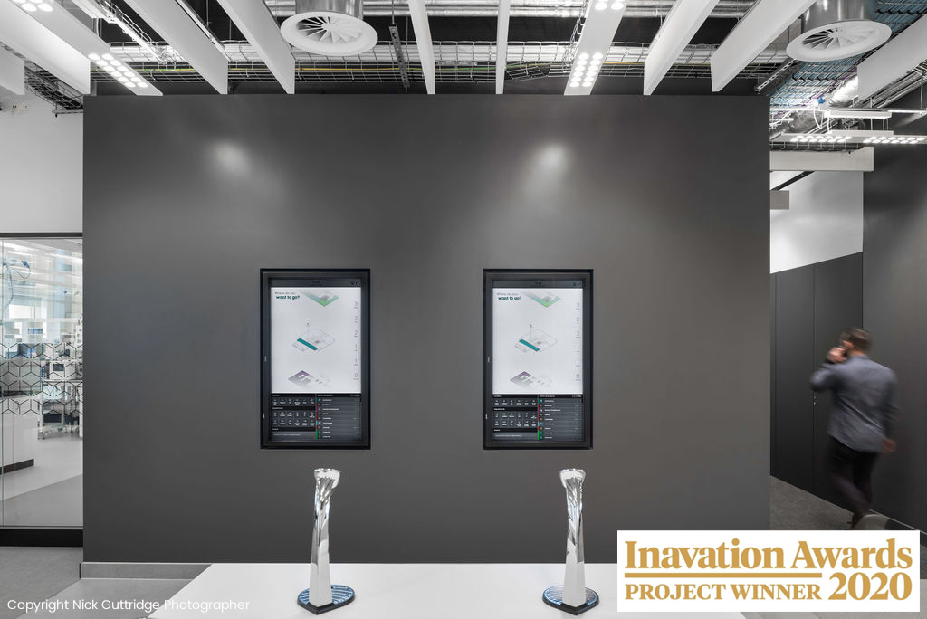 Two interactive touchscreens displayed on a dark grey walled office space with two Inavation Awards for project winner 2020 in front