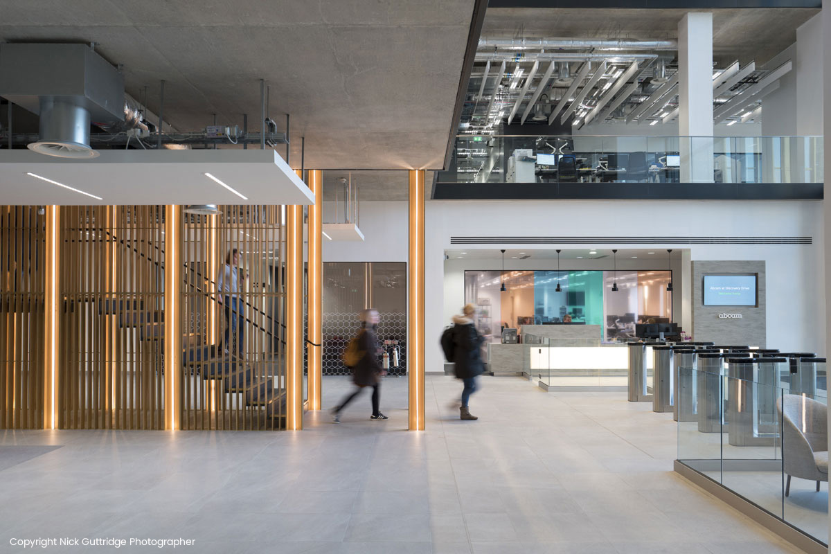 People walking down stairs framed by horizonal lighting towards interactive touchscreen displayed by office exit